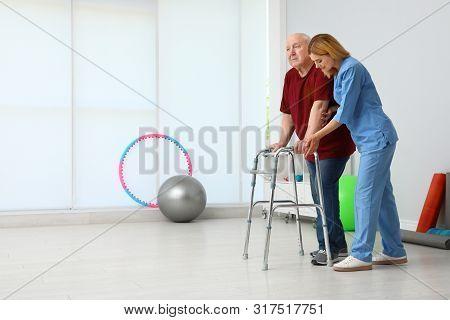 Caretaker Helping Elderly Man With Walking Frame Indoors