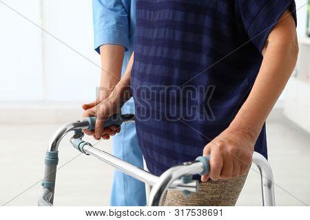 Caretaker Helping Elderly Woman With Walking Frame Indoors, Closeup