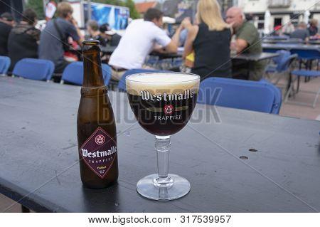 Sint Gillis Waas, Belgium, August 3, 2019, Red-brown Trappist Beer Westmalle. People Enjoy The Beer