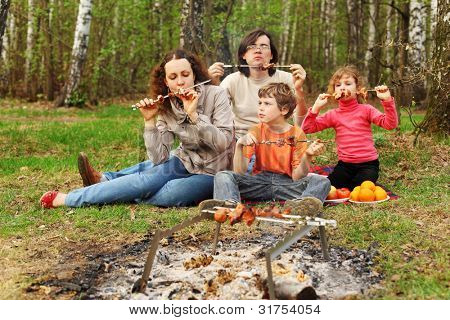 Mother, father and children eat grilled shish kebab outdoor; focus on woman