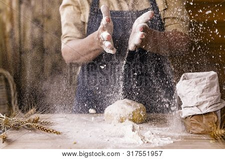 Womens Hands, Flour And Dough. Levitation In A Frame Of Dough And Flour. A Woman In An Apron Is Prep