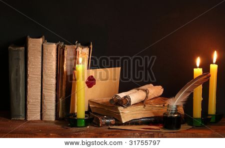 old books, scrolls, feather pen inkwell and candles on wooden table on brown background