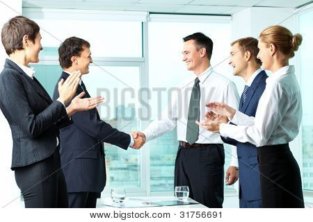 Image of successful co-workers applauding to handshaking men