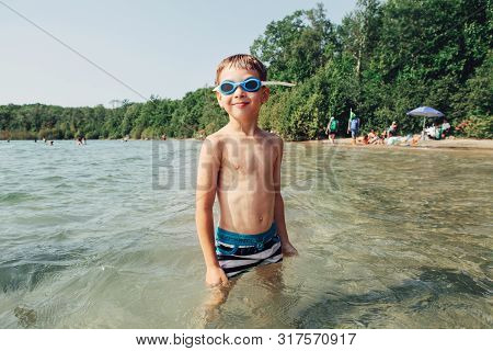 Cute Funny Caucasian Boy Swimming In Lake River With Underwater Goggles. Child Diving In Water On Be