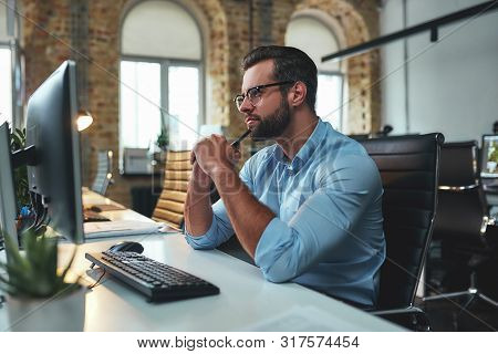 New Ideas. Side View Of Young Bearded Man In Eyeglasses And Formal Wear Looking At Computer And Thin