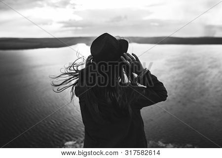 Traveler Girl With Windy Hair Holding Hat And Looking At Evening Sky On Top Of Rock Mountain.lonelin