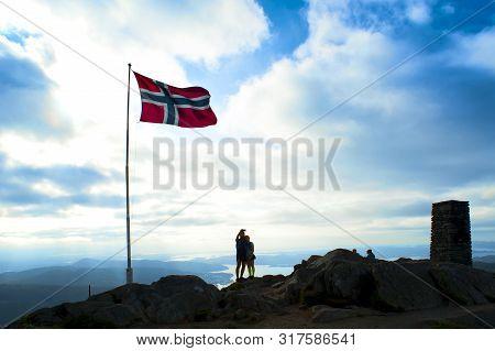 Bergen, Norway - August 4, 2019: Norwegian Flag And Tourists On The Top Of Mount Ulriken In Bergen