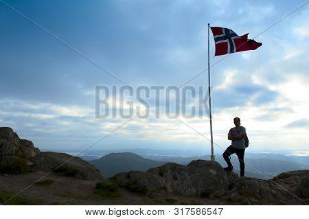 Bergen, Norway - August 4, 2019: Norwegian Flag And Tourist On The Top Of Mount Ulriken In Bergen
