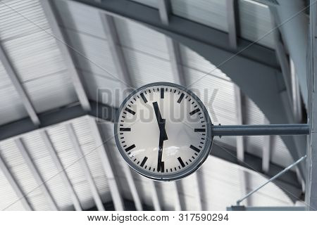 Public Clock In Railway Station At The Hanging With Roof Of Subway Central Train Station. It Is Cloc