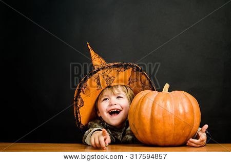 Happy Halloween. Child With Pumpkin. Little Boy In Witch Hat With Halloween Pumpkin Pointing To You.