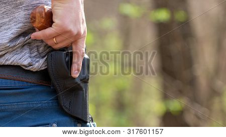 A Man Takes Out A Revolver With A Yellow Handle From A Black Leather Belt Holster