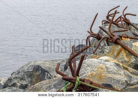 Row Of Old Rusty Anchors On Rocks Along Newfoundland Seacoast