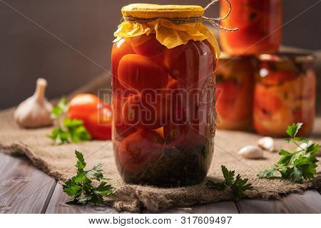 Homemade Jars Of Pickled Tomatoes On A Rustic Wooden Background. Pickled And Canned Product. Next Ot