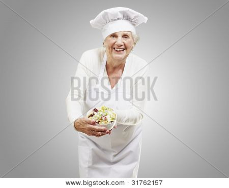 senior woman cook holding a bowl with salad against a grey background