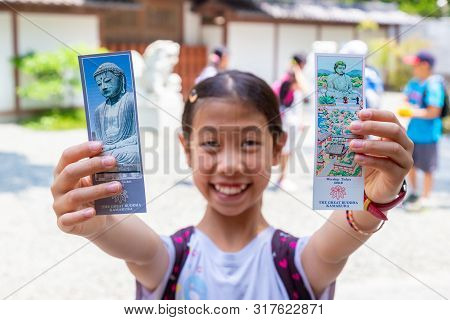 Kamakura, Japan - 15 June 2015 - Happy Asian Girl Holds Temple Entrance Tickets To Visit Buddha Stat