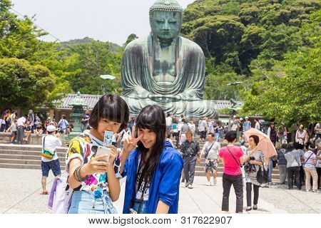 Young Happy Asian Girls Taking Their Selfie In Front Of Famous Buddha Statue Of Kotuku-in Temple