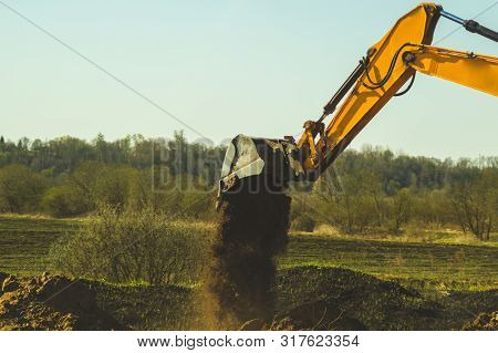 Excavator Digs The Ground. Part Of Construction Earthmoving Equipment. Digging And Filling The Soil