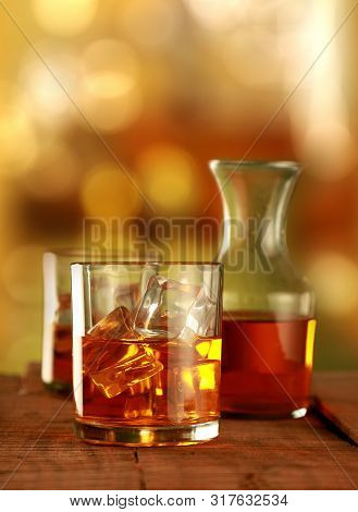 Chilled Whisky Glass With Ice Cubes On Blurred Background