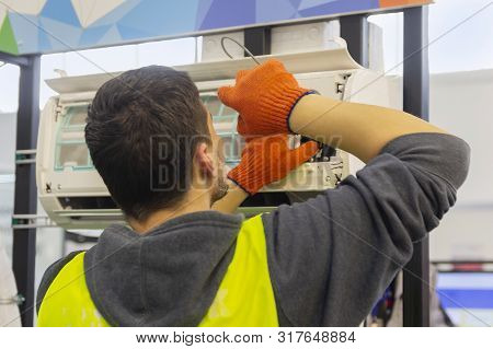 Worker mounts and connects the air conditioner on the wall of the house poster