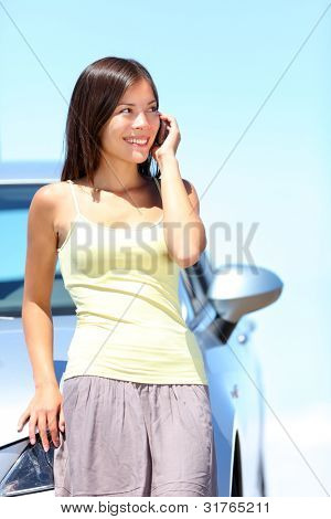 Woman on smart phone by car.  Young woman standing by car talking on mobile phone. Happy smiling mixed race Caucasian Asian woman on a beautiful bright sunny summer day