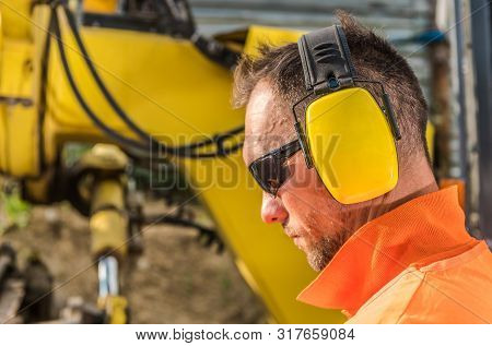 Noise Reduction Hearing Protection Headset. Caucasian Construction Contractor Wearing Sunglasses And