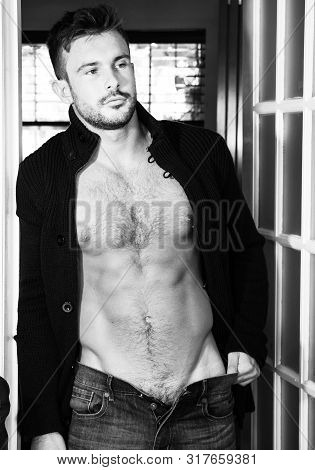 Attractive Young Man Standing In Doorway With Muscular Abs And Unbuttoned Jeans.