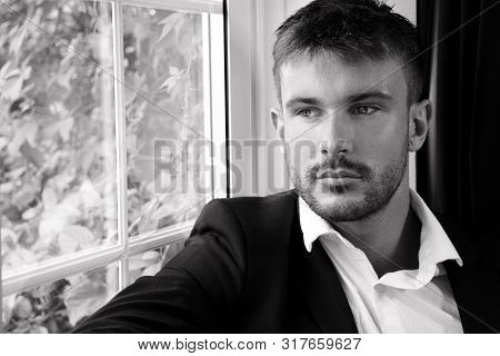 Attractive Man With Beard Wearing Shirt And Jacket Sitting And Looking Out Of Window