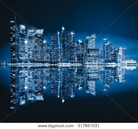 Singapore Downtown Skyline At Night With Reflection. Financial District And Business Centers In Tech