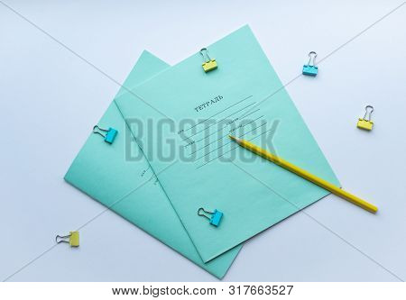 Top View Of Two Pupils Copybooks With Form To Sign In: Name, Surname, Grade, Etc. With Yellow Pencil