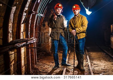 Two Miners In The Mine. Hard Work In A Coal Mine. Copy Space. Tired Workers In A Coal Mine