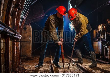 Two Miners In The Mine. Copy Space. Hard Work In A Coal Mine. Tired Workers In A Coal Mine.