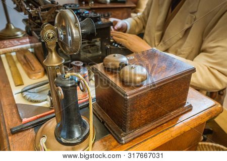 Vintage Antique Candlestick Telephone, Old Typewriter With Hand Of Old Man On Vintage Table.
