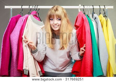 Pretty Happy Woman Between Clothing From Wardrobe. Young Undecided Shopper Girl Having Fun And Bough