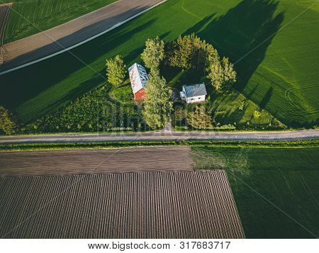 Aerial View Of Farmland With Red Barn And Houses And Harvest Field In Finland