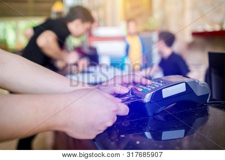 Hand put credit card In slot of credit card reader with blurry cashier and customer at counter servi