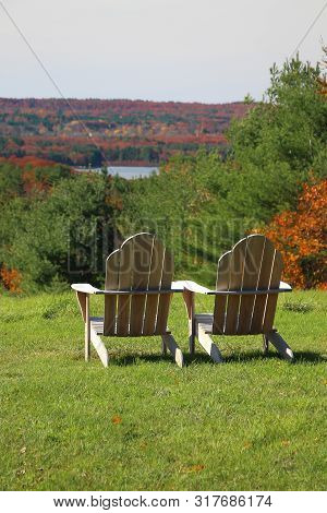 Wooden Adirondack Chairs In Vertical With Lush Green Grass And Fall Colors Showing In The Overlook
