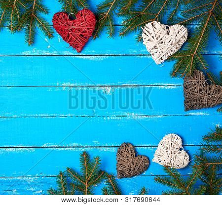 Green Branches Of Needles And Decorative Wicker Hearts On A Blue Wooden Background From Boards, Fest