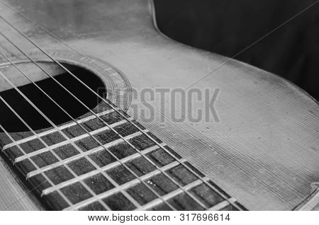 Details Of An Old Acoustic Guitar, The Body Curves, Sound Hole, Frets And Nylon Strings. Wooden Acou