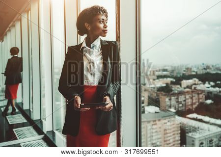 An African-american Woman Entrepreneur A Digital Tablet Is Leaning Against A Panoramic Window Of An