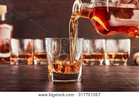 A Glass Of Whiskey On A Wooden Table In Which Poured Whiskey From A Bottle. In The Background Are Fo