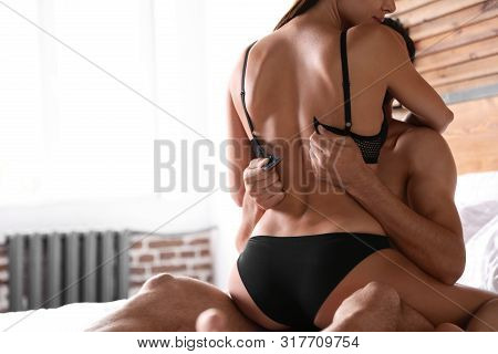Passionate Young Couple Having Sex On Bed At Home, Closeup