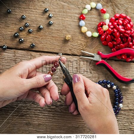 Jewelry Making. Making Bracelet Of Colorful Beads. Female Hands With A Tool On A Rough Wooden Table.