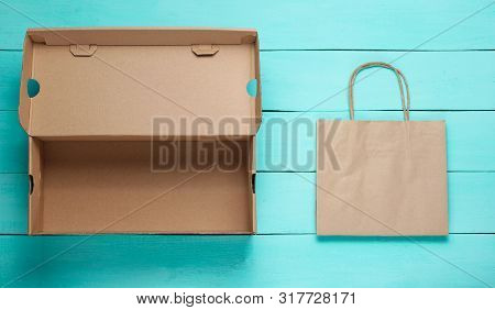 Empty Cardboard Box And Paper Bag On Blue Wooden Background. Ecology Concept.  Top View