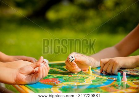 Board Game And Kids Leisure Concept. Kids Are Playing. People Holding Figures In Hand. Yellow, Blue,