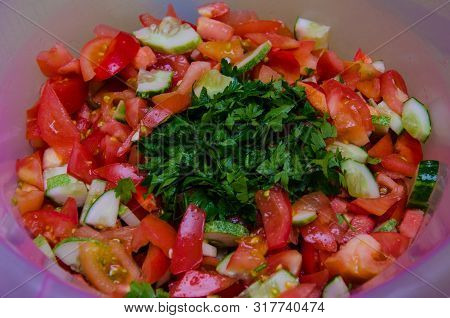 Multi-layered Vegetable Salad With Hazelnuts On A Blue Dish On A Blue Tablecloth With A Pattern