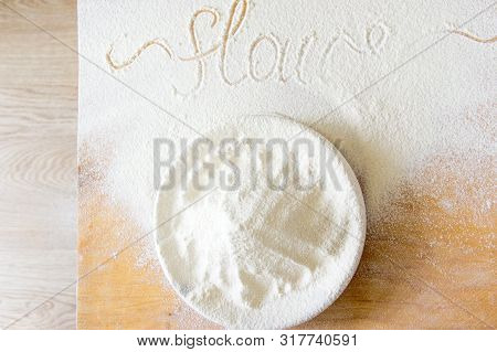 Bowl With Flour On Wooden Texture. Word Flour Written From Hand And Floured