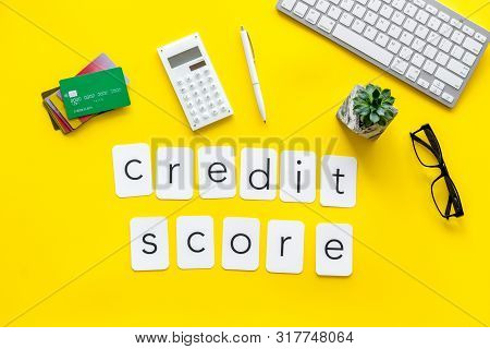 credit score text with credit cards and keyboard on banker work place yellow background top view poster