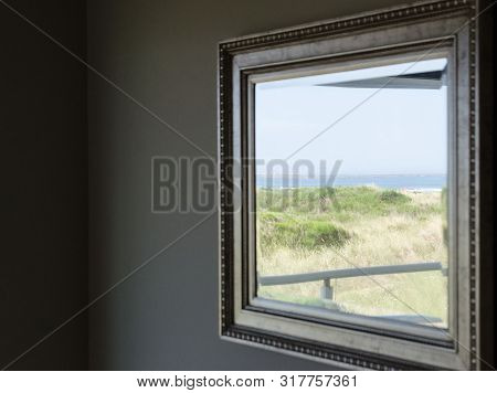 Reflection Of Dunes And Beachgoers  In A Mirror In Metal Frame Inside Apartment Near Westport State