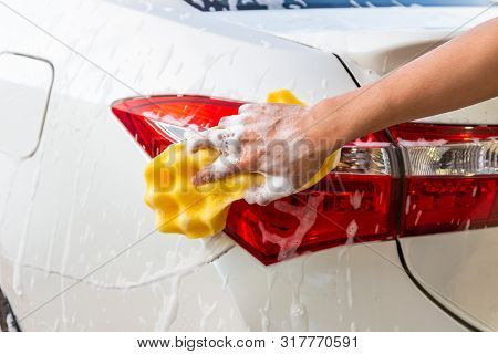Woman Hand With Yellow Sponge Washing Taillight Modern Car Or Cleaning Automobile. Car Wash Concept