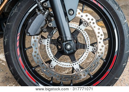 Front Wheel Close Up Of Brakes System In A Modern Motorcycle Modern With Disc Brakes.